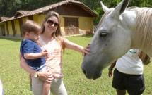 Mãe e Filho Fazendo Carinho no Cavalo Black