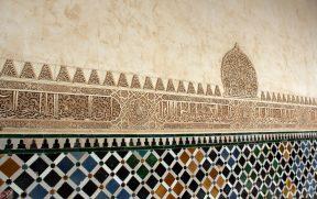 Paredes com friso em árabe entre azulejos e arabescos