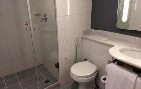Banheiro com chuveiro no teto e espelho iluminado