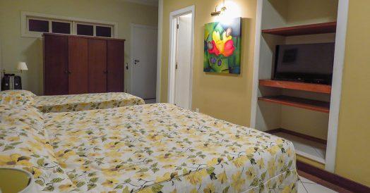 Cama de casal, armário e TV em quarto amplo
