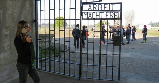 Jaque ouvindo o áudio-guia na entrada do campo de concentração
