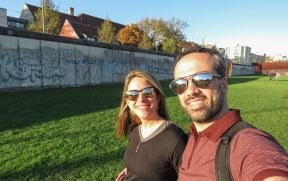 Casal ao lado do Muro de Berlim