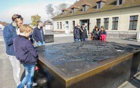 Turistas vendo o mapa de Sachsenhausen ao lado do Centro de Visitantes